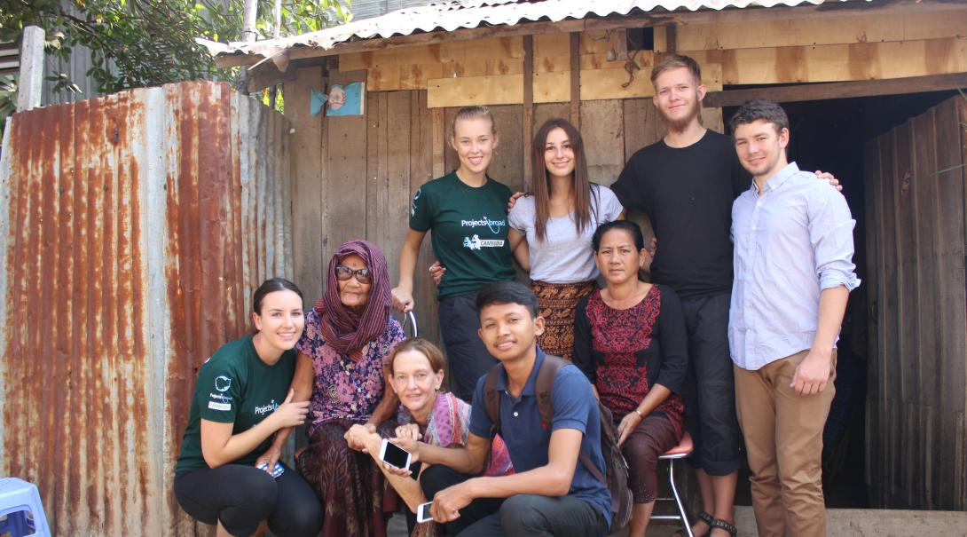 Volunteers take a group photo with a local family during their time abroad